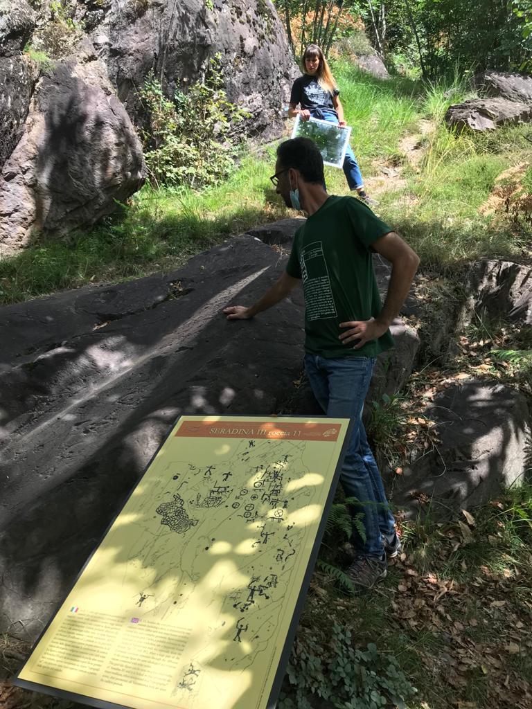 Marretta e Salvetti mostrano  una roccia sul percorso marrone indossando le magliette del MetaParco di Seradina-Bedolina